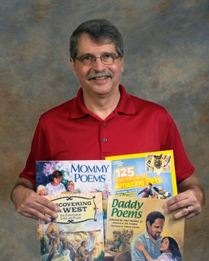 photo of John J. Micklos Jr. with some of his published books
